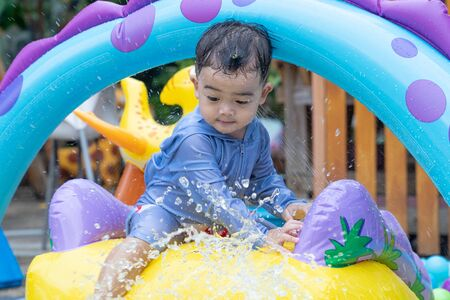 Asian cute baby boy playing in inflatable baby pool. Kids swim and splash in colorful garden play center. Happy little girl playing with water toys on hot summer day. Family having fun outdoors in the backyard. Stay at home.