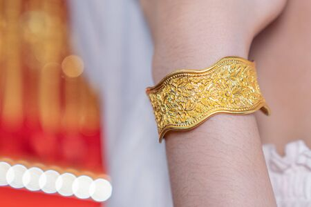 Luxury gold bracelet, Golden bracelet on arm background. Traditional of china for Wealth and Good Fortune.