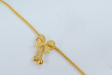 Close up. Beautiful golden bow necklace jewelery on white background. Beauty and accessories.