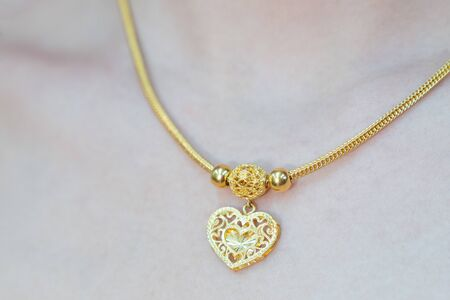 Close up. Beautiful neck girl with gold necklace. Woman in a golden heart necklace jewelery. Beauty and accessories.