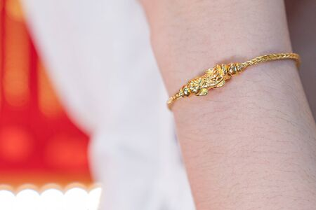 Luxury gold bracelet, Golden Dragon Pixiu or Pi Yao on arm background. Traditional of china for Wealth and Good Fortune.