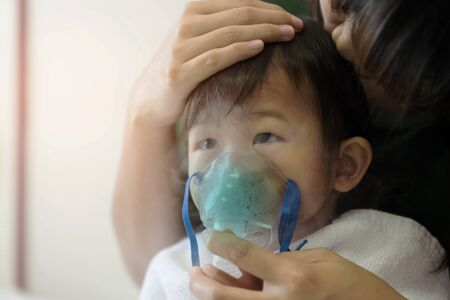 Close up. Asian baby girl breathing treatment with mother take care, at room hospital. Health care kid concept.