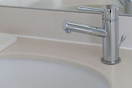 Modern stainless water tap in white bathroom sink, luxury hotel.