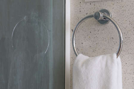 Close up. White and clean towel is hanging on the exposed concrete wall in the bathroom. Stockfoto
