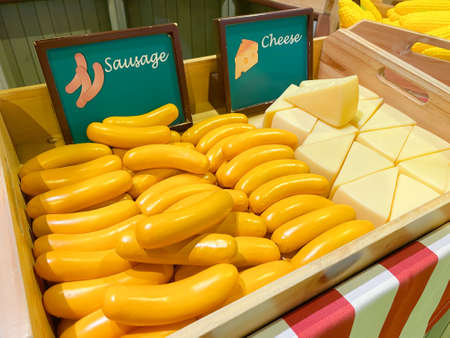 Artificial sausage and cheese in a wooden box as a market design on the background of other vegetables and fruits, soft focus.