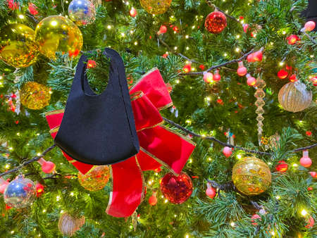 Christmas background with black mask and decorated christmas tree on blurred, sparkling and fairy background.