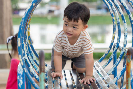 Asian little baby boy enjoy with outdoor zone kid park, climbing steel toy activity on the playground.