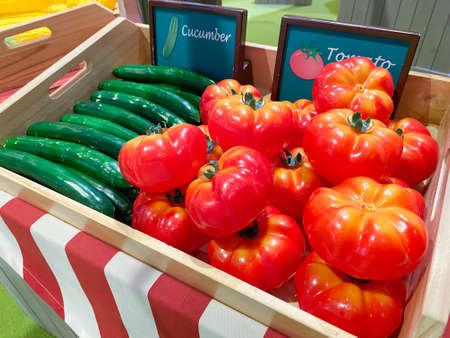 Artificial cucumbers and tomatos in a wooden box as a market design on the background of other vegetables and fruits, soft focus.
