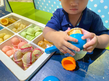 Asian happy child toddler boy playing with toy ice cream.