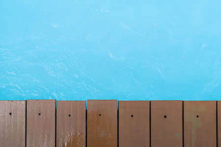 Close up. Swimming pool with teak wood flooring stripes summer vacation.