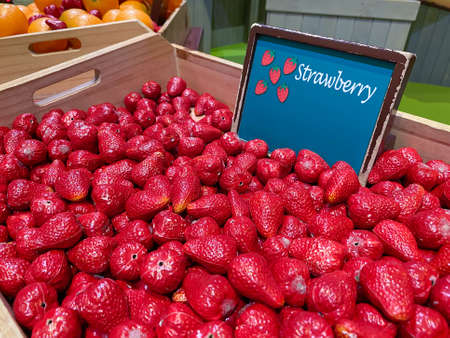 Artificial red strawberrys in a wooden box as a market design on the background of other vegetables and fruits, soft focus.