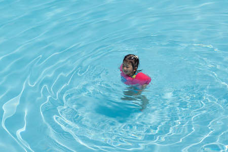 Asian cute little toddler girl in a colorful swimming suit relaxing in a pool having fun during summer vacation in a tropical resort. 版權商用圖片