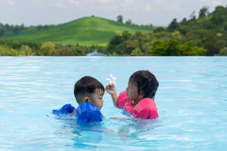 Asian cute little toddler boy and girl in swimming suit relaxing in a pool having fun during summer vacation in a tropical resort, mountain background.