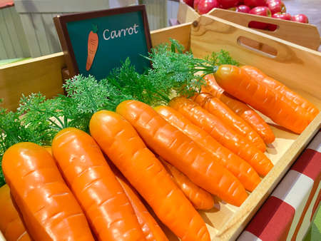 Artificial orange carrots in a wooden box as a market design on the background of other vegetables and fruits, soft focus. 版權商用圖片