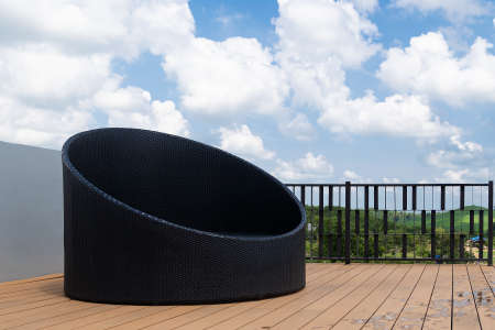 Relax corner with modern black sofa on rooftop luxury resort, blue sky and mountain background.
