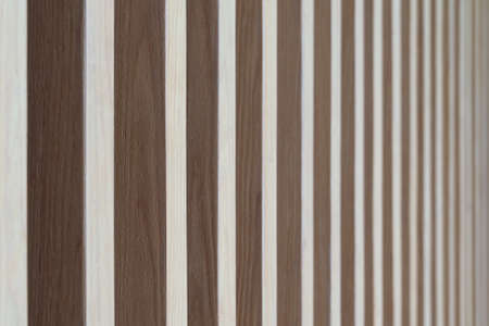 Close up. Seamless pattern of modern wall covering with light brown wooden slats. Background interior design.