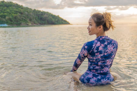 Asian swimwear woman with slim body swimming in sunset sea banner of water copyspace. Travel holiday girl relaxing on beach vacation.