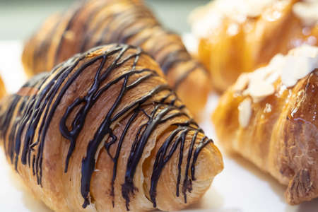 Freshly baked croissants on white dish. Close up. Фото со стока
