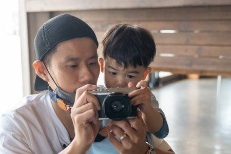 Asian dad is enjoying son taking a photo. 版權商用圖片