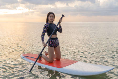 Stand up paddle board woman paddleboarding on beach, Thailand. sitting happy on paddleboard on blue water. Young  Asian female model on Koh Samed beach, Thailand, on summer holidays vacation travel.