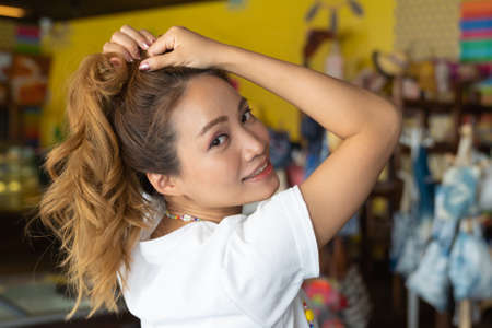 Asian beautiful woman is smiling in cloth shop background.
