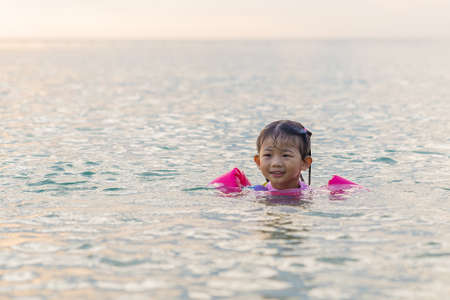 Happy smiling baby girl swimming in the sea, Thailand.