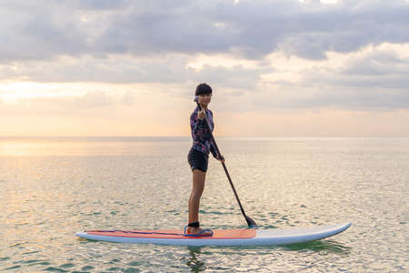 Stand up paddle board woman paddleboarding on beach, Thailand. standing happy on paddleboard on blue water. Young  Asian female model on Koh Samed beach, Thailand, on summer holidays vacation travel. 版權商用圖片
