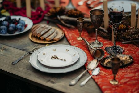 Antique dishes and iron wine glasses on the table with food Banque d'images