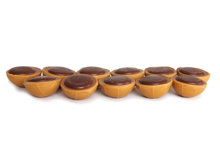 toffee: toffee chocolates arranged in two lines on white background Stock Photo