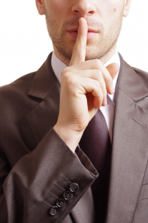 suited man with a gesture of shh on white background