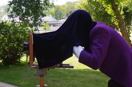 chrome base: un uomo in viola presa in frac foto con una vecchia macchina fotografica in legno su un treppiede