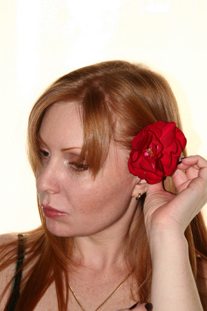 puts: woman puts a rose in hair. white background