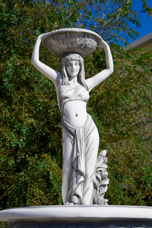 woman statue, who holds plate
