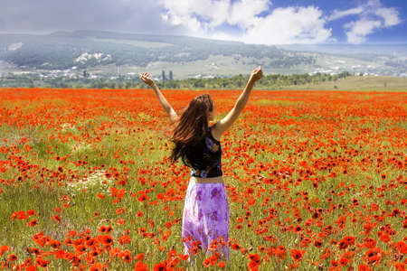 The girl on a meadow with blossoming poppies Stock Photo