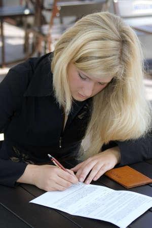 bussines: Het blonde meisje de ondertekening van het contract van belang