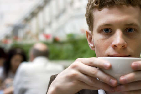 The young man drinking coffee in cafe Stock Photo