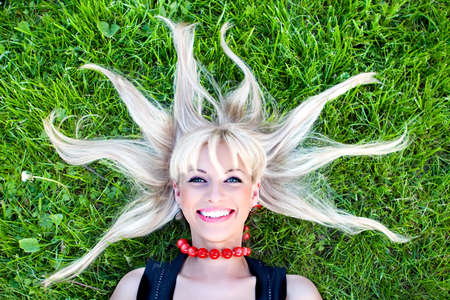 The beautiful blonde laying on a grass with scattered hair
