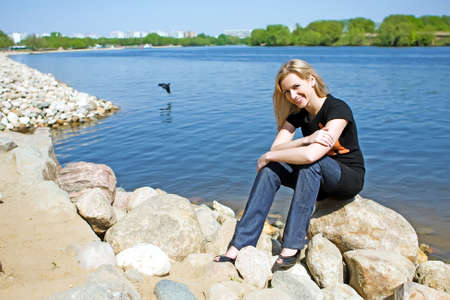 The beautiful girl on the bank of the summer river photo