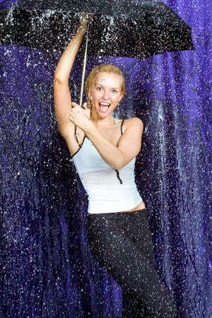 The beautiful girl under the stylised rain in studio photo