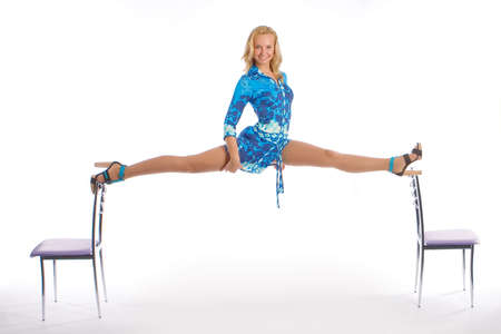 The beautiful young girl does a splits between backs of chairs