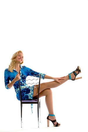The beautiful blonde posing in photosession with a chair photo