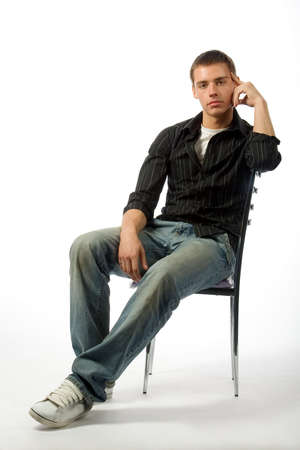 The thoughtful young man on a chair Stock Photo