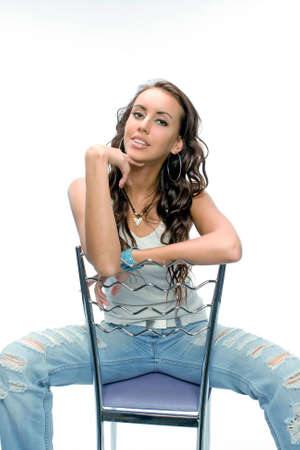 The beautiful brunette posing in photosession with a chair Stock Photo - 3200191