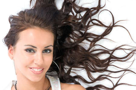 The beautiful girl laying on white with scattered hair Stock Photo