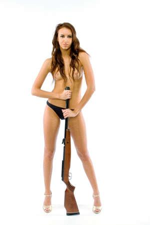 La bella ragazza topless con un fucile su sfondo bianco
