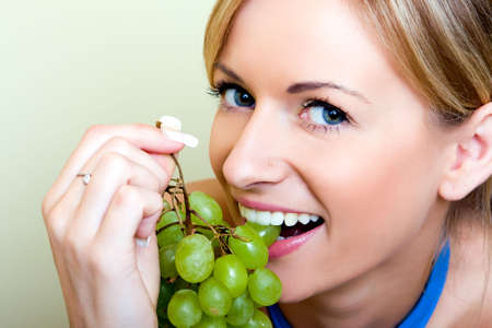 Beautiful young woman with green grape photo