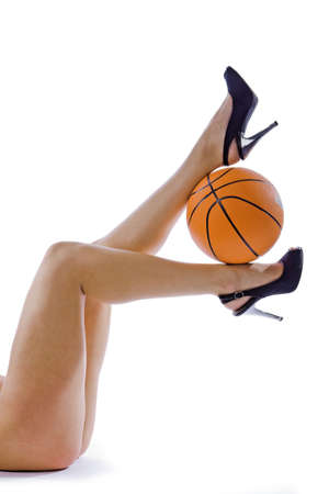 The beautiful legs of the young girl and the basketball ball