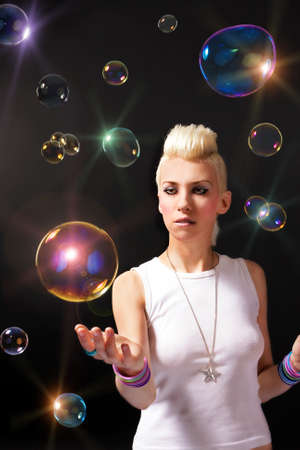 Beautiful girl with blonde hair and soap bubbles photo