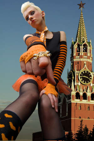 Young beautiful blonde in the background of the Kremlin on Red Square in Moscow pointing at something with his finger