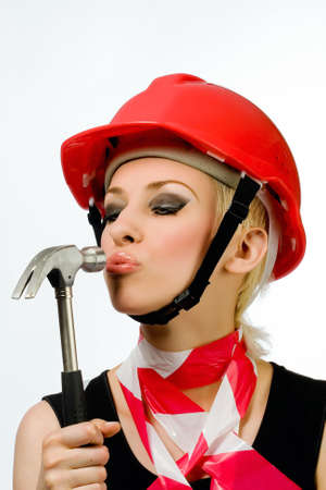 A beautiful girl with a hammer and a construction helmet